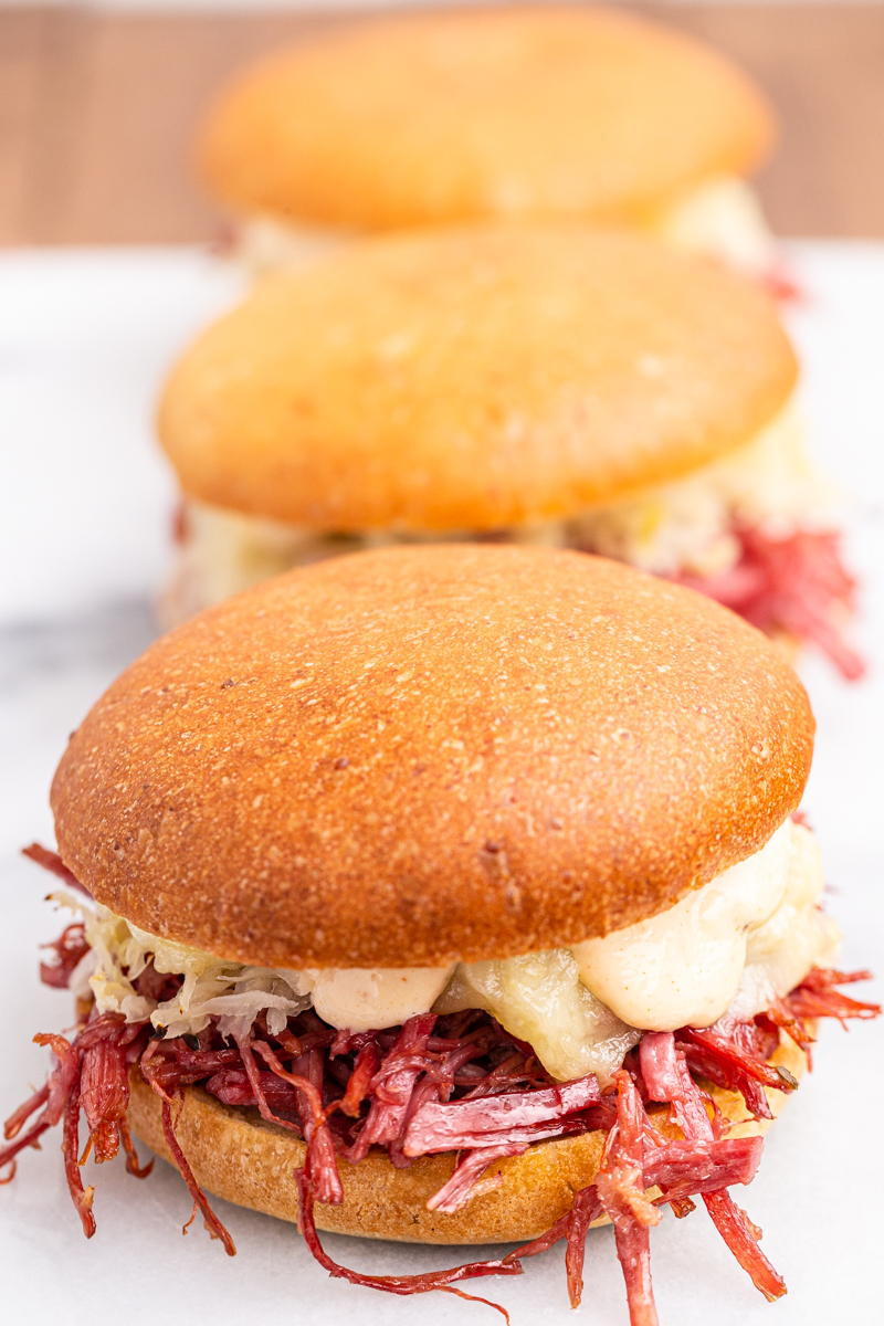 Close up photo of 3 Keto Reuben Sliders on a white platter.