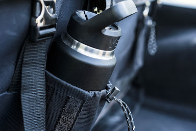 An black insulated cup, made by Yeti, resting in the side pocket of a backpack.