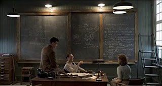 Two men and a woman sit in front of a blackboard covered with scientific equations