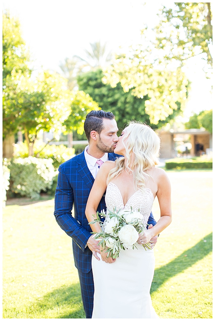 bride in two piece wedding dress and groom in custom blue suit kissing at Arizona Biltmore