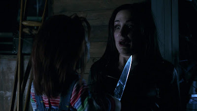 Movie still from the movie Curse of Chucky where Chucky holds a knife in Barb's (Danielle Bisutti) face