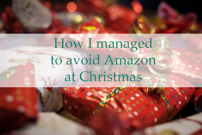 "A pile of presents with red and gold wrapping paper, with a white banner across the middle and ""How I managed to avoid Amazon for Christmas"" in green text."