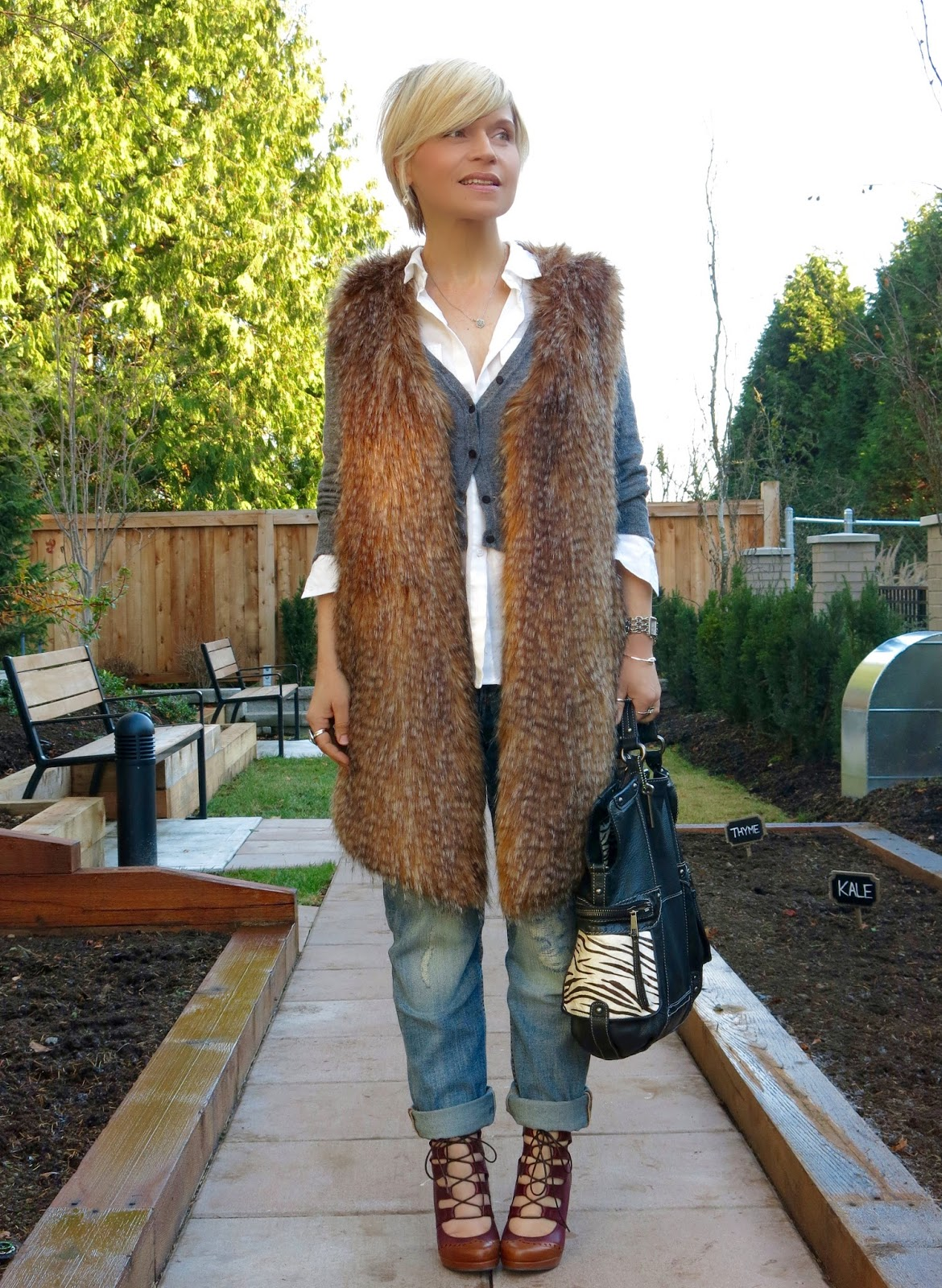 styling boyfriend jeans with a white shirt, shrunken cardigan, furry vest, and lace-up shoes