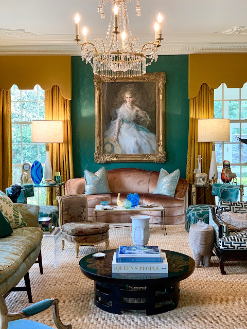 Emerald green living room walls and marigold draperies in a sumptuously luxurious interior with crystal chandelier.