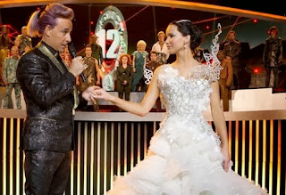 Stanley Tucci as Caesar Flickerman and Jennifer Lawrence as Katniss Everdeen in The Hunger Games: Catching Fire (2013), Directed by Francis Lawrence