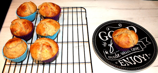 6 low fat banana muffins cooling on a cooling rack; one muffin on a plate, ready to eat while it is still warm