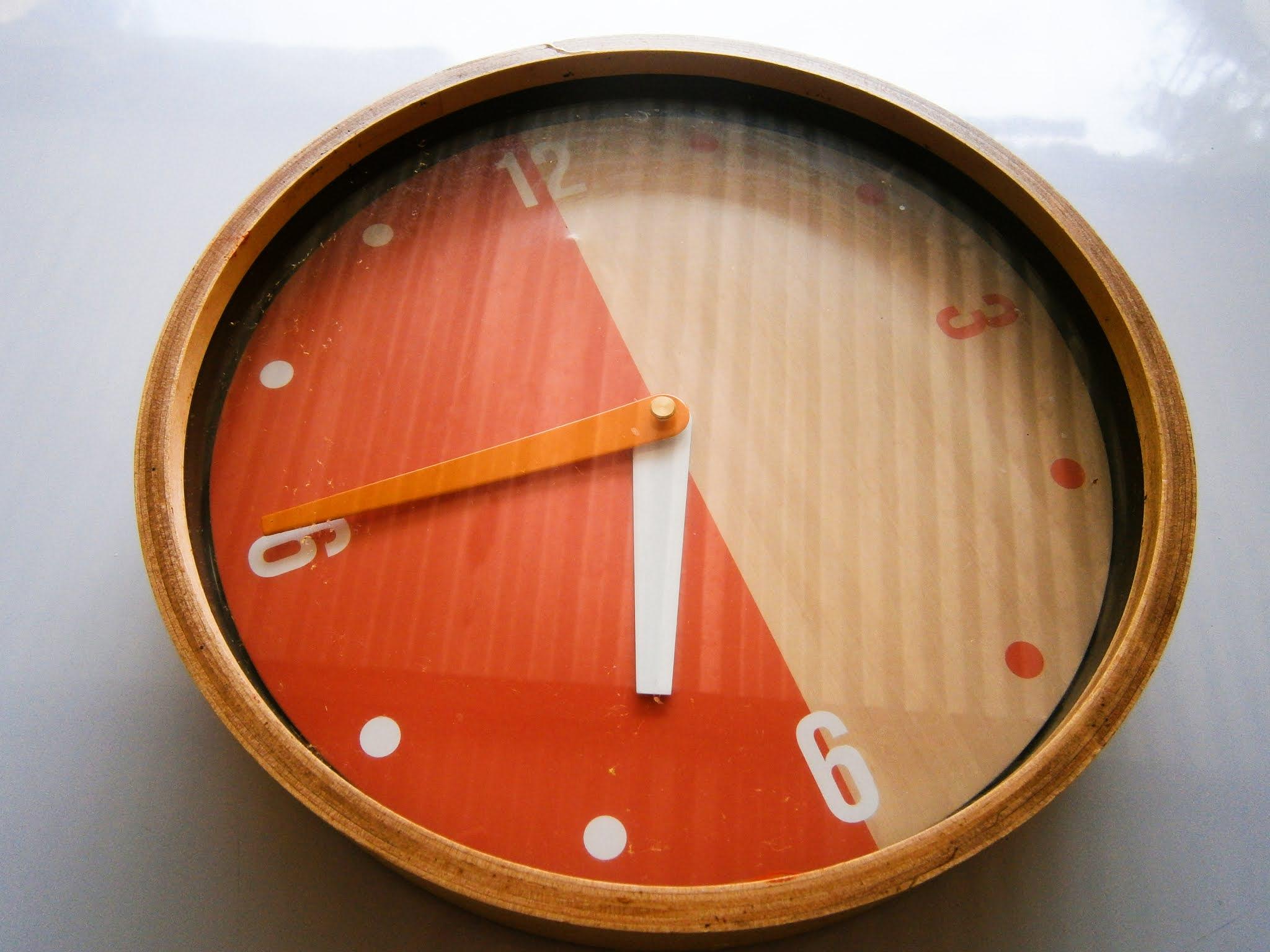 Reloj de madera puesto sobre un fondo de color blanco