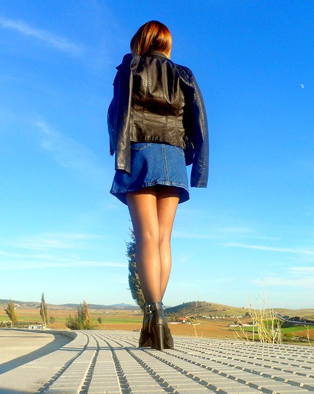 Falda denim acamapanda, jersey de punto rasgado, cazadora biker negra y botines de tacón con hebillas