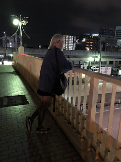Silver haired girl wearing denim jacket standing on a bridge at night