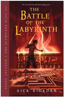 A boy (Percy) holding a sword stands over a glowing coffin, a labyrinth stretches behind him