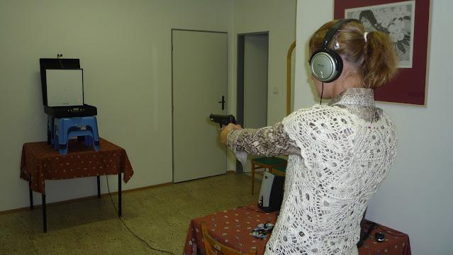Linda míří na terč laserovou pistolí (zvuková střelba)