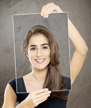 Une femme tient une photo d'elle souriante