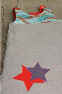 Turbulette en lin coloris naturel, coton japonais, violet au dos et rouge intérieur, appliqués étoiles, fermeture éclair beige sur le coté, pressions turquoises épaules, doublée en ouatine longueur 70 cm (0-3 mois).