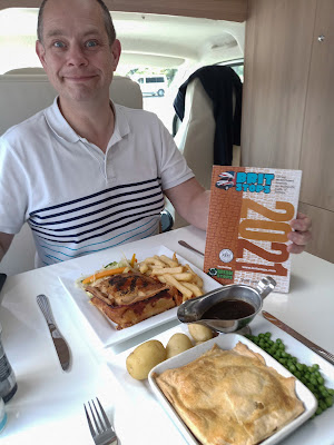 Neil sitting at the table in our motorhome,  with our dinner (2 pies) served up ready to eat. He is holding the BritStops book in his hand.
