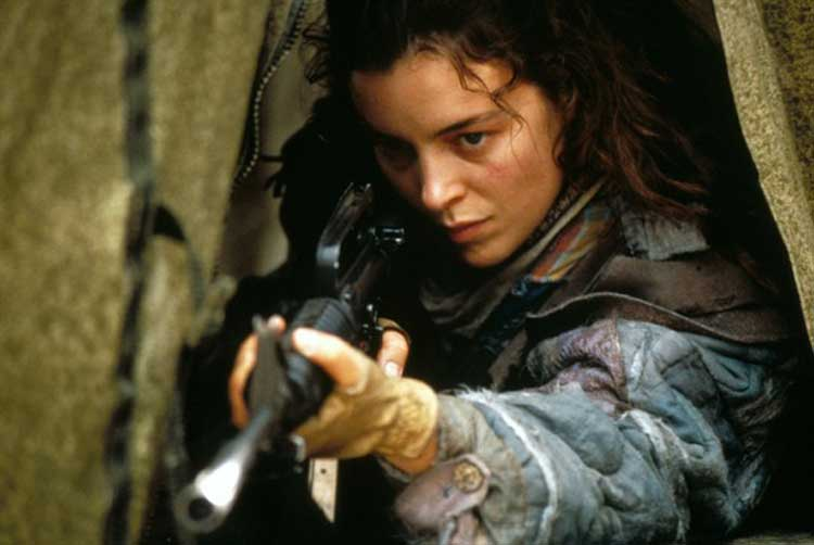 Olivia Williams grabs a gun in The Postman.