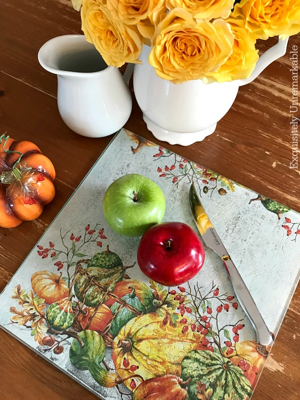 Napkin covered glass cutting board on table with fruit and flowers