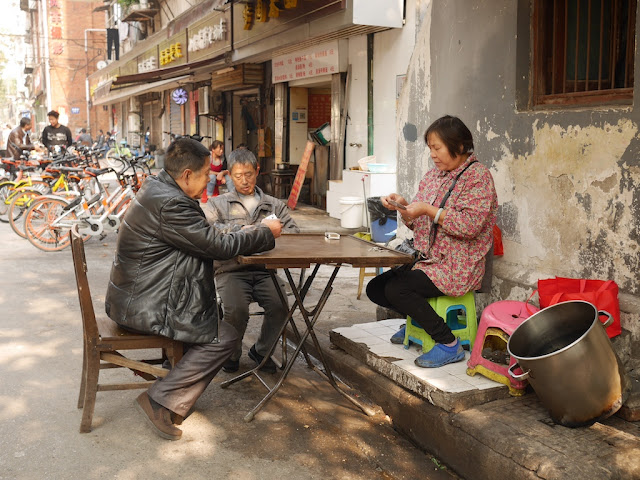 three people playing a card game on a sidewalk in Wuhan
