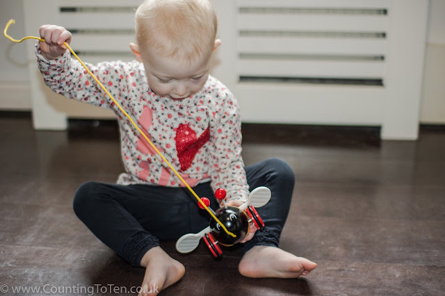 A toddler playing with the Brio Pull Along Bumblebee