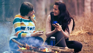 Two women sitting in a forest in front of a camp fire, chatting