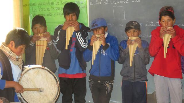 Schüler die auf Zampoñas pfeifen