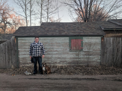 A man and his dog in front of an old shed.