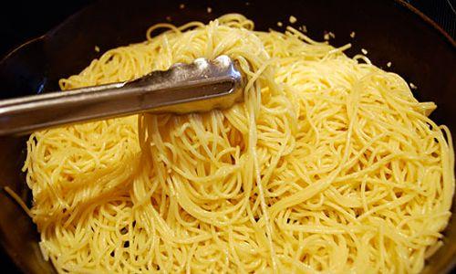 Sirviendo espaguetis o tallarines, con una pinza de pasta