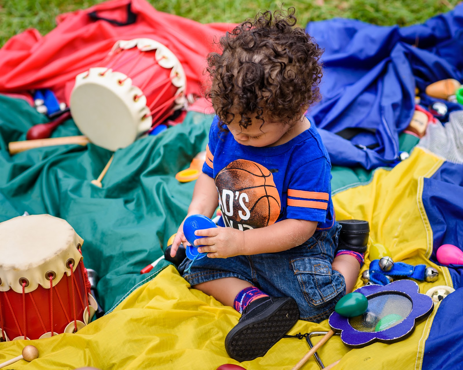 boy focused on instrument at Music Together Vivo! Park Playalong © Diana Sherblom Photography