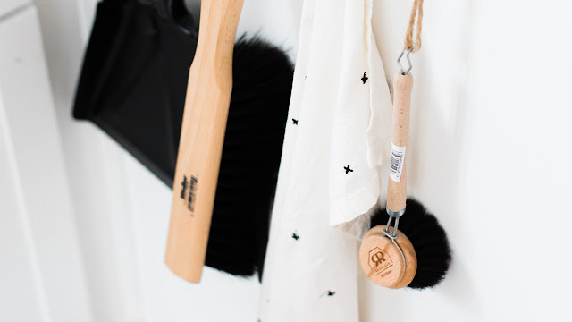 Cleaning implements like a scrub brush and dust pan and towel hanging on hooks.