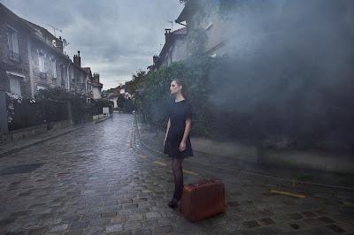 Chica vestida de negro con su maleta en las calles de un pruebo con niebla