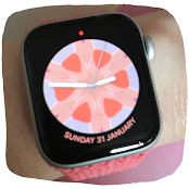 Photo of my Apple Watch. The strap is pink braided. The watch face is now different to the pervious photograph and now shows a digital analog clock with a pink and orange kaleidoscope watch face along with the date along the bottom of the round clock face.