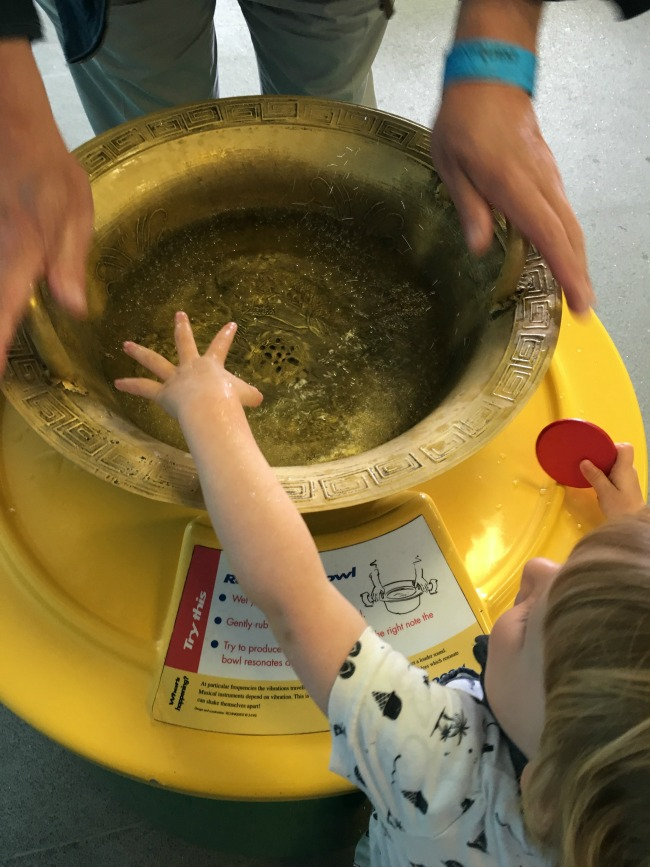 toddler-with-hand-in-water-that-is-vibrating-due-to-resonance