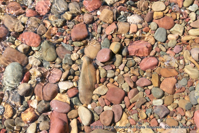 Colorful pebbles in the shallow water at the shore's edge.