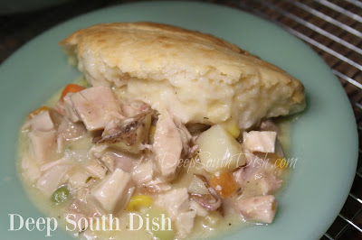 Chicken Pot Pie Casserole with a filling made of pre-cooked chicken, cream soup and chicken broth, mixed vegetables and a few herbs and seasonings, topped with a biscuit batter.