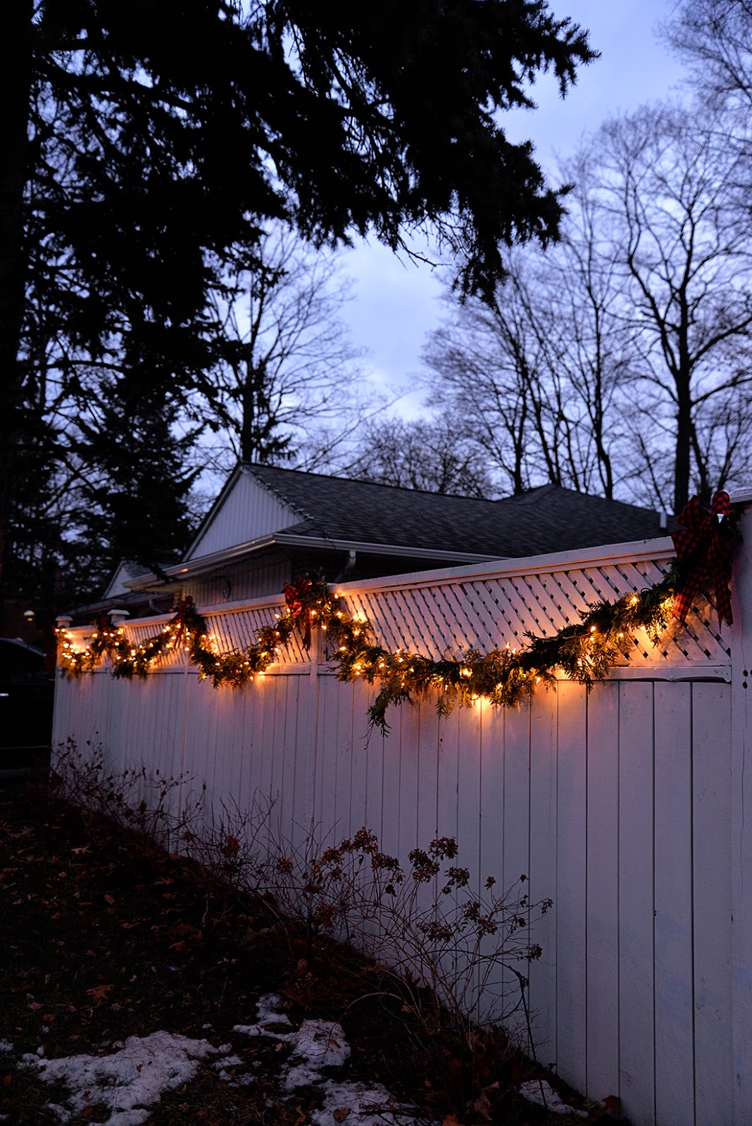 white house decorated with white christmas lights, Christmas fence garland, cedar garland roping