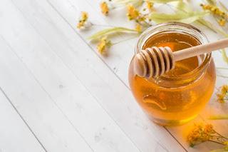 وعاء عسل مع ملعقة خشبية