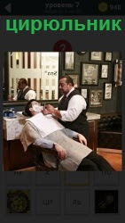 В помещении парикмахерской цирюльник бреет мужчину около большого зеркала в кресле вытянув ноги