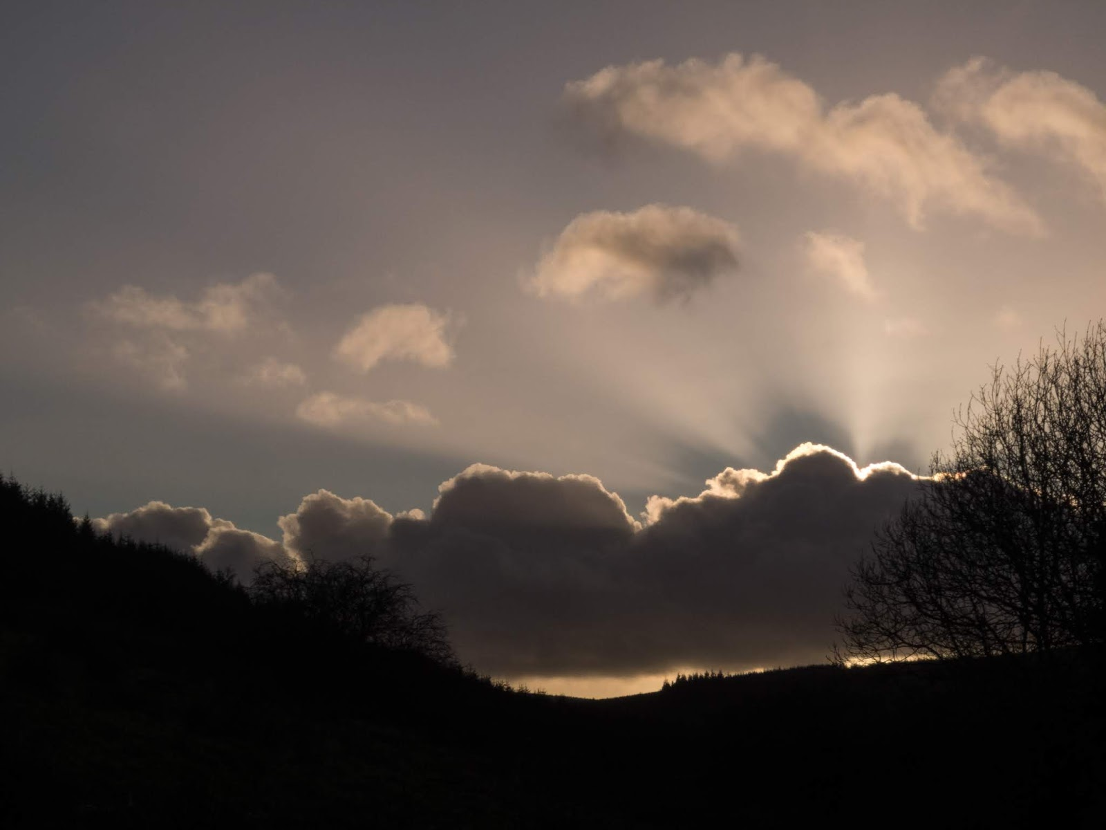 Sun beaming over the top of a cloud in a valley in North Cork.