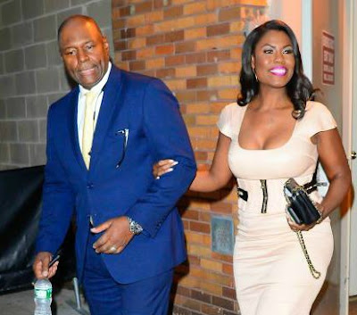 John Allen Newman's wife Omarosa holding his hand while coming outside
