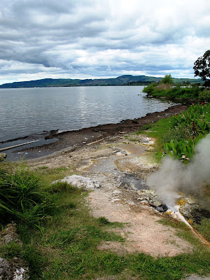 View over a lake, with a geothermal outlet pipe in the foreground.