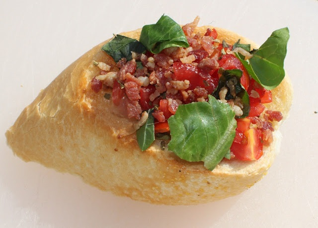 this is baguette bread topped with cooked bacon, tomato and basil