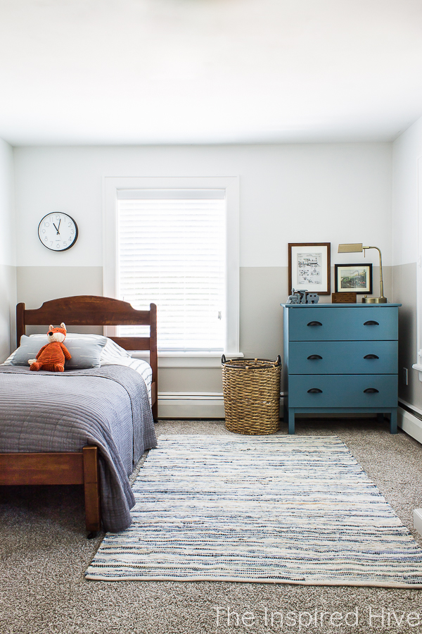 Boy's bedroom with antique bed and blue dresser