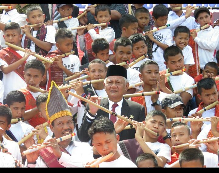 Bupati Toba Samosir Darwin Siagian saat memainkan alat musik tradisional Batak yakni seruling dengan lihainya diacara HUT Kabupaten Toba Samosir ke-20.
