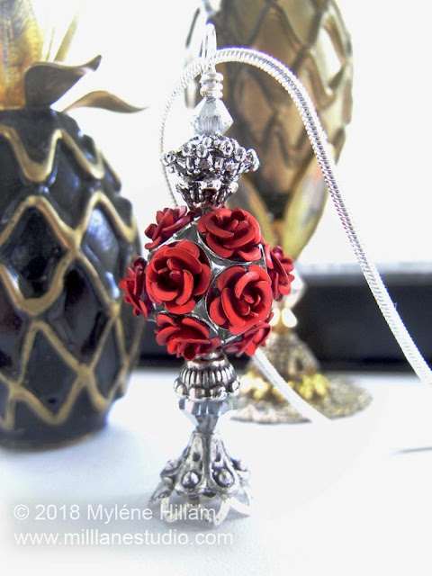 Bottle necklace made with a red rose cluster bead and bead caps.