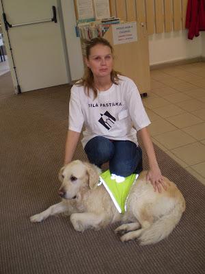Linda v tričku Bílá pastelka sedí na bobku, před ní leží se zlatý retrívr Cilka