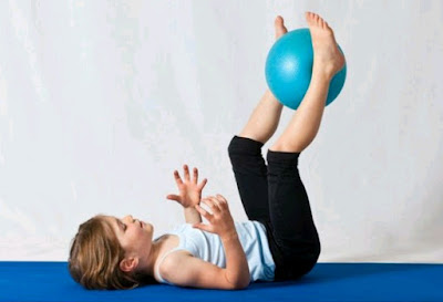 A kid exercising with a fitness ball