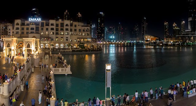 The image shows Downtown Dubai at night. There is a creek in the middle of the downtown area, and lots of people and lights surrounding it