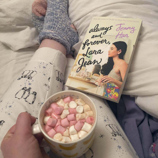 Cover of 'Always and Forever, Lara Jean' by Jenny Han next to a hot chocolate with marshmallows and penguin pajamas