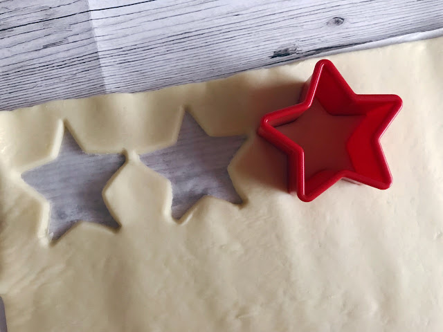 Pastry rolled out and being cutout with a star shaped cutter