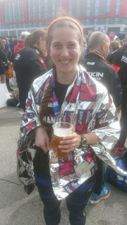 a smiling white woman stands wrapped in silver foil, holding a pint of isotonic beer