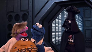 """Sesame Street Cookie's Crumby Pictures Star S'mores. Cookie Monster, starring as """"Flan Solo,"""" struggles to not eat his partner, a sentient cookie named """"Chewie""""."""